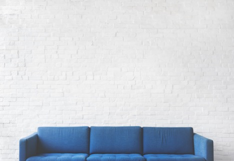 A navy blue sofa against a white background